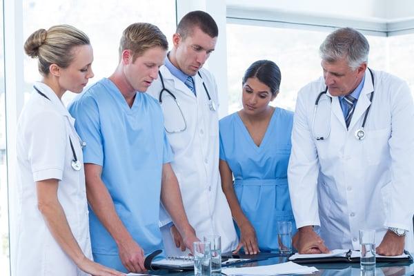 Team of doctors looking at their diaries in the meeting room